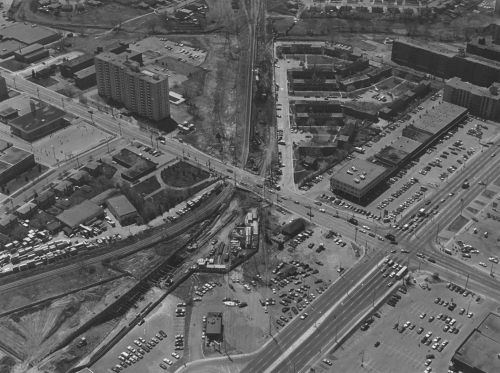 Foreground shows work site. Background shows parking lots, apartment buildings and other building types.