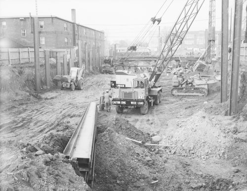 Heavy machinery in excavated trench. PCC streetcar and brick buildings in background.