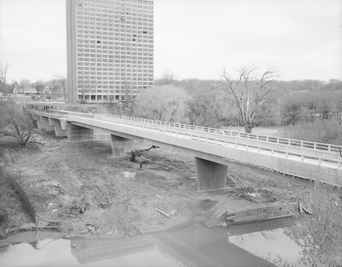 Completion of construction of trackbed on bridge. Background shows trees and construction of tall building.