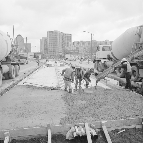 Four men laying concrete into prepared middle area of the road. Background shows office towers and condominiums.