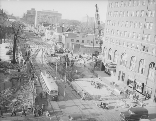 PCC on streetcar tracks at lights, traffic, in background heavy machinery in operation between buildings.