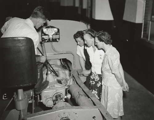 Three women looking at a bus motor with instructor pointing at motor part.