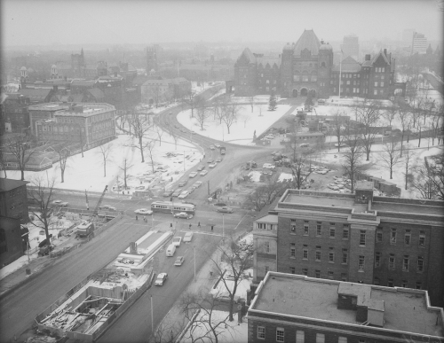 Winter scene showing streetcar, cars, and excavated area for tunnel construction. Foreground shows multi-storied building and background shows Parliament Buildings