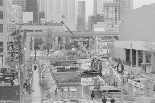 Installation of beams above excavated area. Foreground shows people on pedestrian passageway. Background shows office towers.