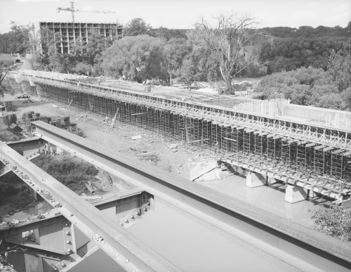 Installation of structural supports for bridge. Background shows trees and erection of structure for building.