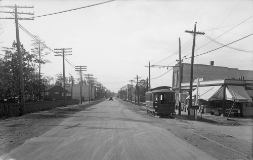 A streetcar drives along a wide road. On the right is a row of stores with large awnings.