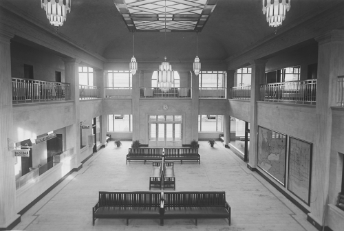 A waiting room that is two storeys high, with a stained glass skylight and large hanging chandeliers. The walls contain ticket windows and framed maps. There are several benches in the middle of the room.