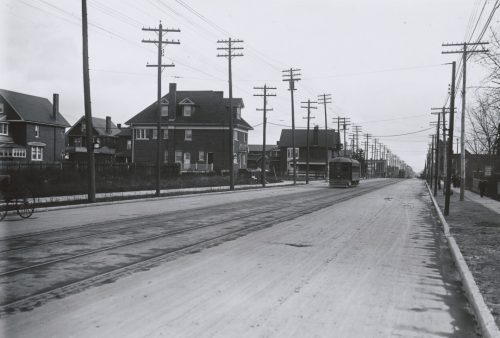 A streetcar drives down a street lined with telegraph and electricity poles. There are large houses in the distance.