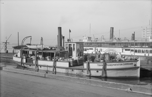A wooden boat with its deck filled with boxes and parcels sits at a wide wooden dock.