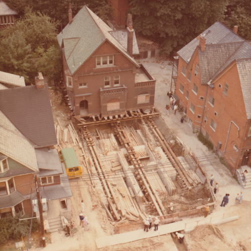 Three storey brick building removed from its foundation by rollers. House foundation can be seen with house roller mechanism.