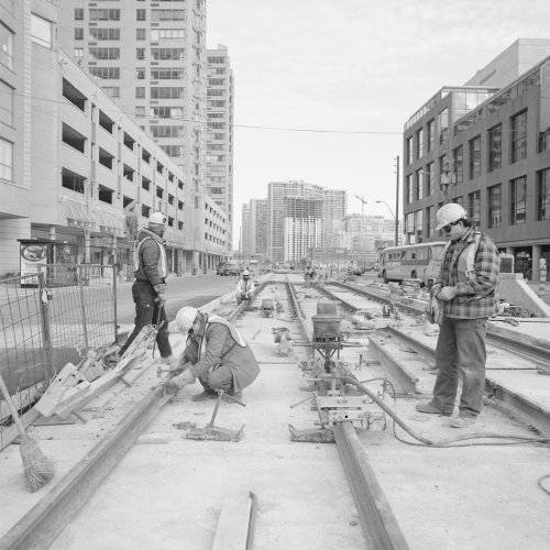 Three men installing streetcar rail in newly formed trackbed. Background contains office building, parking garages, and condominiums.