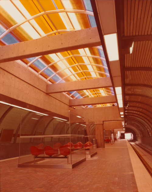 Finished platform with seating and coloured artwork at ceiling.