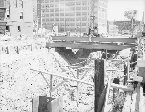 Cross section showing excavation under road decking being placed at road and multi-storied buildings in the background