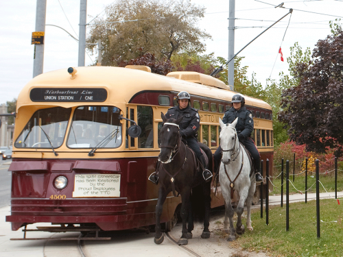 Two police on brown and white horses ride beside a red and yellow painted streetcar.