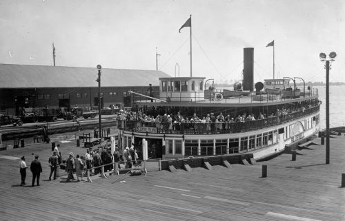 People are boarding a large wooden ferry on a wide wooden pier. People line the railing of the open upper deck.