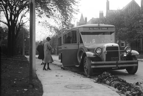 Woman boarding bus from sidewalk.