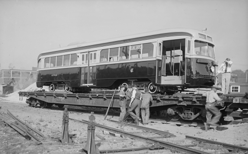 Workers are gathered around a shiny streetcar that sits on an open train car bed.