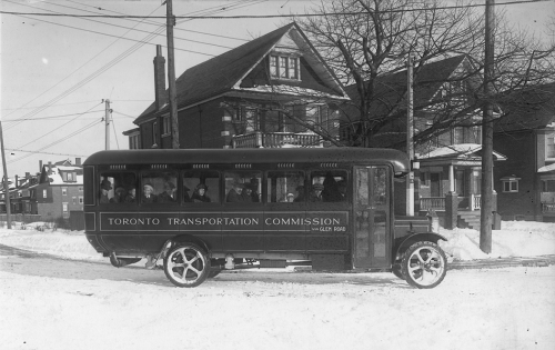 A small bus drives down a road in winter. There are detached three-storey houses behind it.