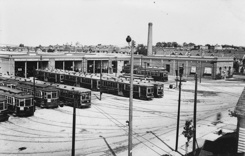 Several streetcars stand in a row outside of a low brick building with large garage doors.
