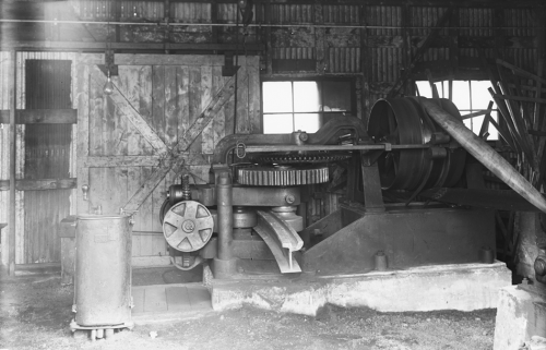 A large machine with many cogs and wheels. A piece of metal streetcar track shaped like an I-beam is sticking out of it.