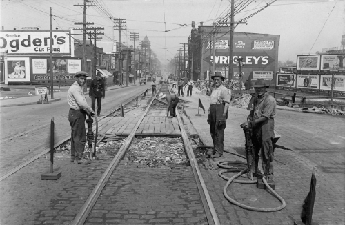 Men with jackhammers are breaking up the brick road around streetcar tracks.