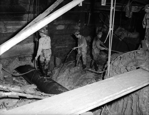 Workers are standing on a pipe and in a torrent of water in an underground excavation.
