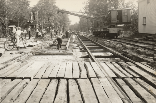 Large square timbers are laid in rows between streetcar tracks on a road.