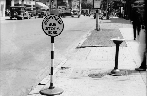 """A round sign on top of a shoulder-high pole. It says """"Runnymede bus stops here."""""""
