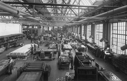 Interior of a large factory with big windows. Workers are assembling the stops of streetcars.