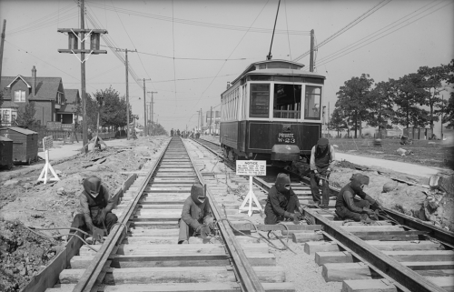 A row of men wearing metal welding helmets are putting together two sets of streetcar tracks on a road.