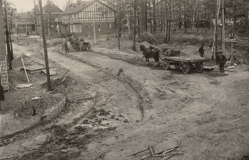 Horse-drawn wagons stand beside a curved ditch excavated in the road for streetcar track construction.