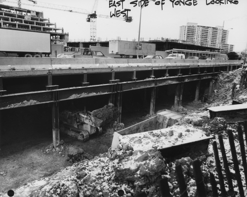 Cross section of tunnel construction under Yonge Street, cars moving above excavated area, and construction Of North York Civic Centre.