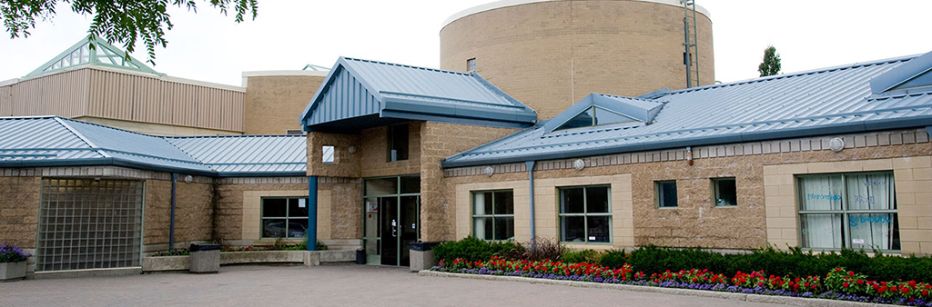 The exterior of Goulding Community Centre which shows the entrance, blue metal roof structure and planting beds with colourful flowers lining the exterior.
