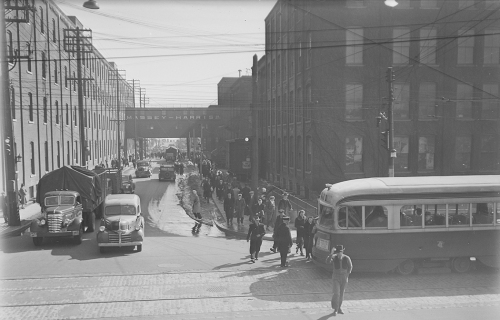 Crowd of people going to streetcar. Background shows large industrial brick buildings.