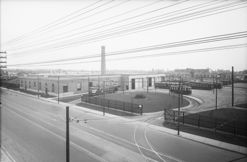 A low brick building with a large smokestack in the back. A streetcar is driving on a loop of track surrounding a grass lawn in the front.