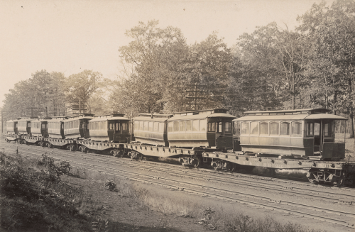 A long line of flat, roofless train cars with streetcars on them.
