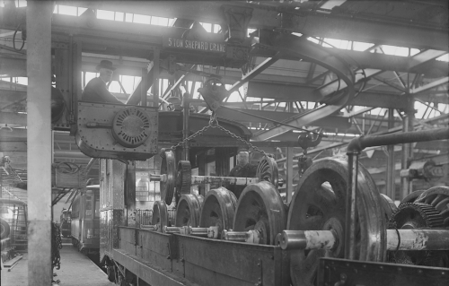 A worker in the bucket of a crane puts large metal wheels onto the bed of an open train car.