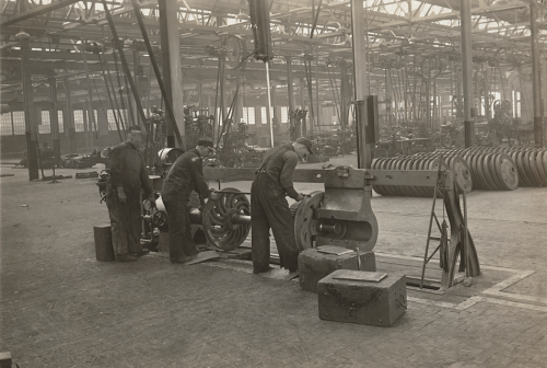 Workers are fitting metal wheels on to a small machine. Behind them is a large warehouse filled with metal wheels.