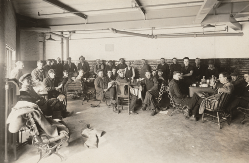 A group of men sit at tables and on wooden chairs and benches in the corner of an industrial-looking room.