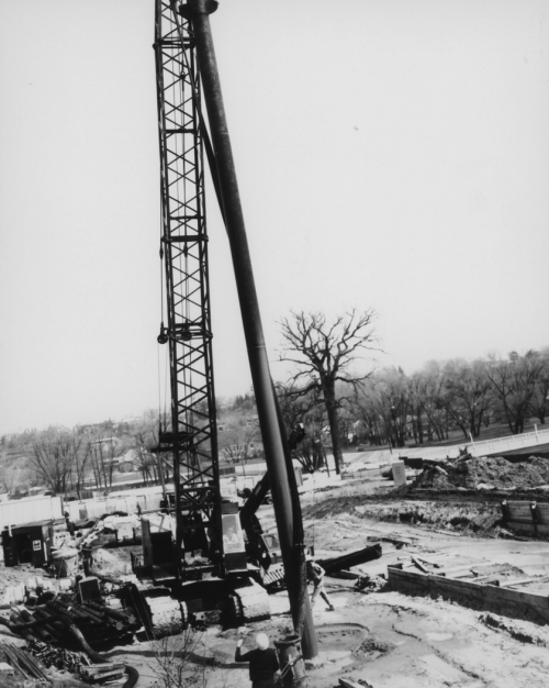 Man standing near large operating drill and heavy machinery.