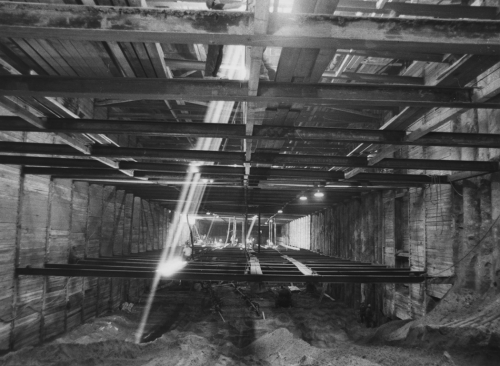 Horizontal beams installed in box tunnel structure. Light shaft coming through ceiling.