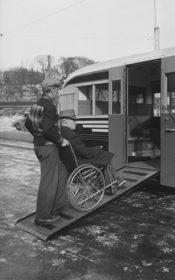 A man is sitting in a wheelchair. Another man is pushing the chair up a wooden ramp into a bus.
