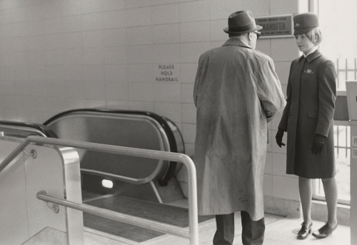 Uniformed woman with older man in trench coat standing at the top of an escalator.