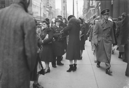 Crowded bus stop with woman offering assistance to woman buying TTC tickets.