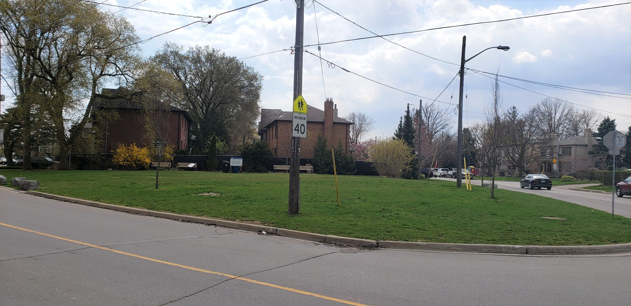 An image of the location for the new parkette taken in the early spring. The site is currently an open lawn area with four benches, light and traffic sign posts and is oval in shape bordered by a concrete edge and surrounded by a residential road and homes.