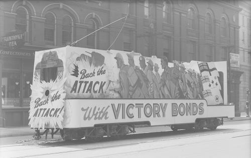 Victory Bonds sign attached to TTC vehicle. Background shows brick building storefronts.