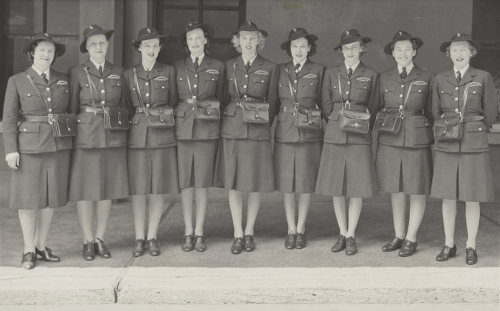 Group of nine women in uniform with hats and over the shoulder bags.