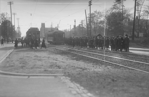Two streetcars sit side by side on the tracks. A line of people is leaving one and lining up to board the other.