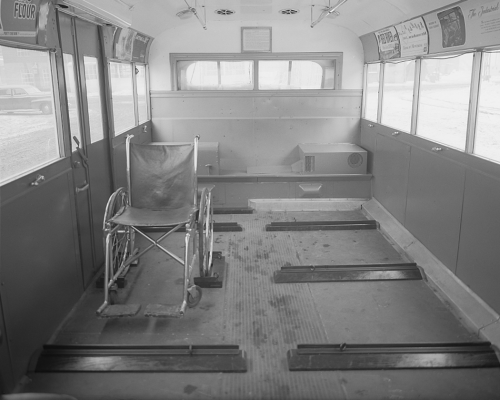 The interior of a bus. Seats have been taken out and replaced with flat spaces and bumpers. An empty wheelchair is sitting in one of the spaces.