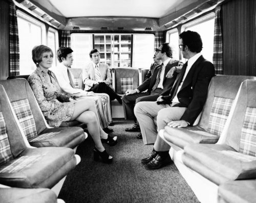 People are sitting inside a van that has wood panelling, plaid curtains, and bucket seats with paid accents facing across the aisle.